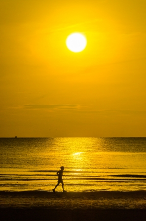running man on the beach in the sunset time photo