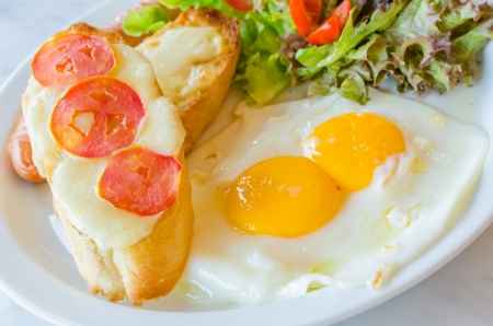 papas doradas: Conjunto del desayuno, huevo frito, salchichas, pan con tomate y queso Foto de archivo