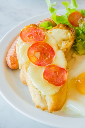 Breakfast set , fried egg , sausage , bread with tomato and cheese photo