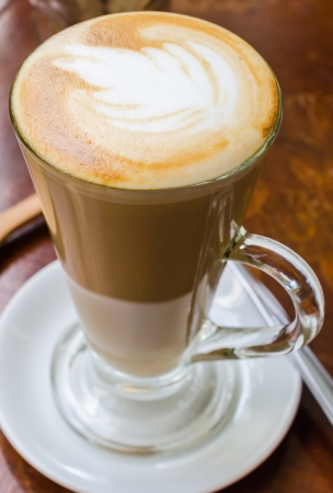 古典的な木製のテーブルにコーヒーを熱いラテ