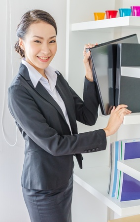 Young business women choose file in office with smiling photo