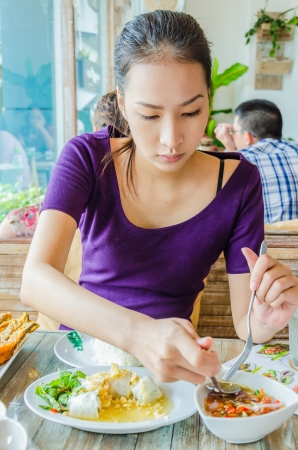 Girl in restuarant in eating action photo