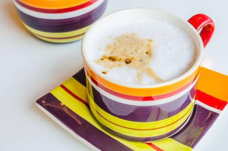 Cappuccino in colorful cup on white table photo