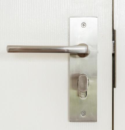 Metal knob on white door photo