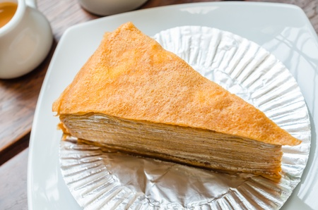 Crepe cake in white dish on the wood table with sweet sauce photo
