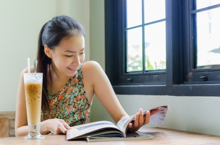 Girl reading a book with ice coffee photo