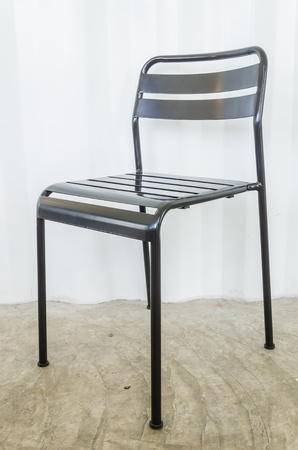 Black metal chair on gray wall photo