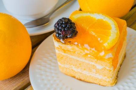 strawberry cake: Orange Cake in white dish on the wood table