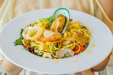 Spaghetti seafood in white dish on the stone table photo