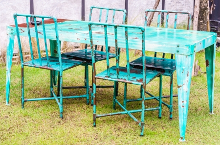Old table and chair on green glass photo