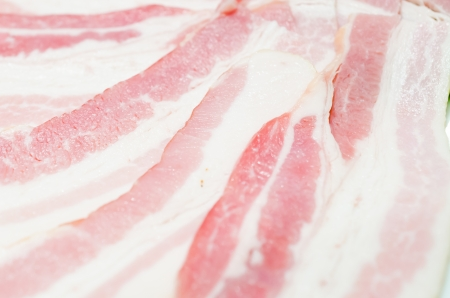 Raw bacon in white dish photo