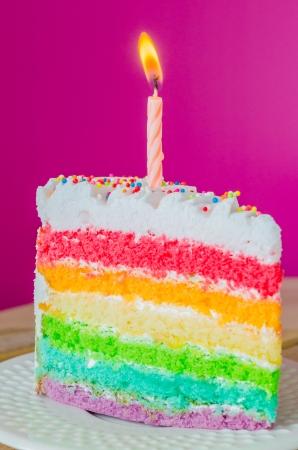 rebanada de pastel: Pastel de arco iris con la vela en un plato blanco Foto de archivo