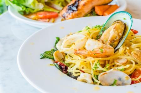 Spaghetti frutti di mare in piatto bianco sul tavolo di pietra