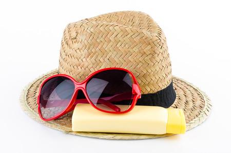 Hut, Sonnenbrille und Bodylotion auf weißem Hintergrund