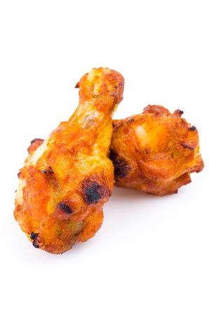 Spicy chicken drumsticks on white background