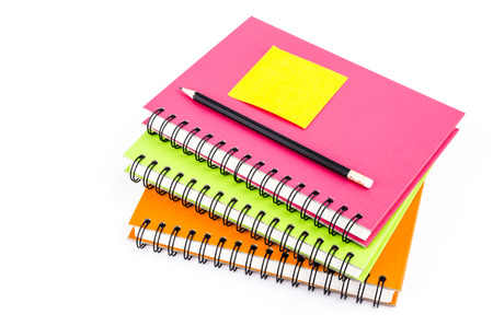 Note pad on notebook and pencil on isolated white background photo