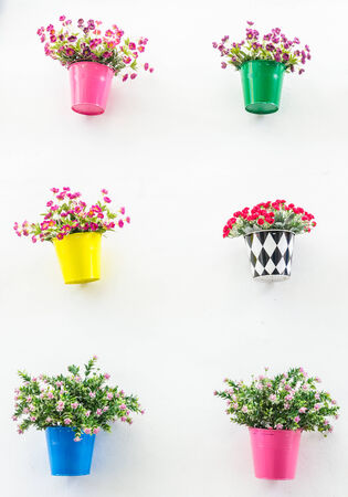 Plastic flower in vase on wall background photo