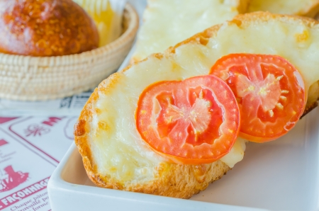 Cheese bread with tomato on top in white dish photo
