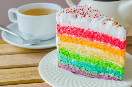Rainbow cake with white tea cup on the wood table photo