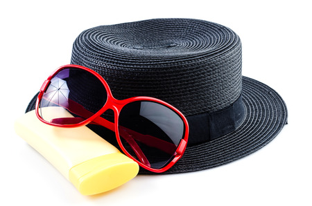 Beach accessories , sunglasses , vintage women hat , body lotion , on isolated white background photo