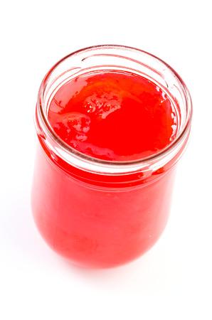 Strawberry jam bottle on isolated white  photo