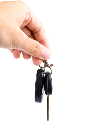 Hand holding Car key on isolated white background photo
