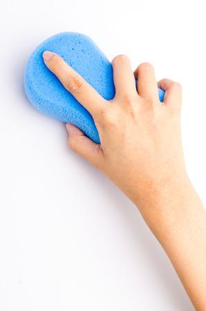 Hand holding sponge on isolated white background photo