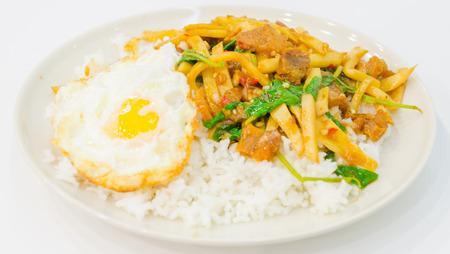 Fried shoot , crispy pork on rice with fried egg photo