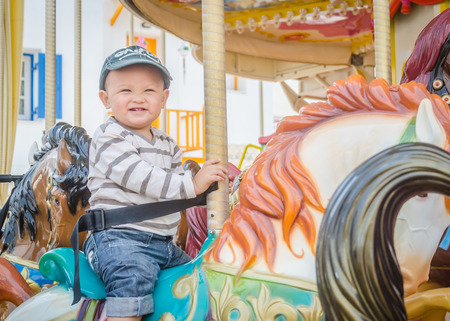 children play: Children play carousel horse Stock Photo