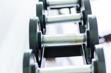 Gym equipment background with close up selective focus to a dumbbell Stock Photo
