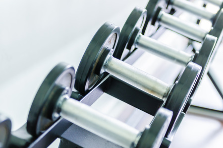 Gym equipment with close up selective focus to a dumbbell