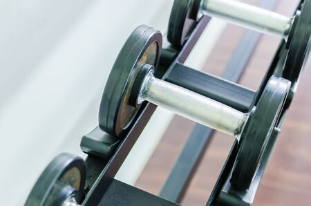 adjustable dumbbell: Gym equipment background with close up selective focus to a dumbbell Stock Photo