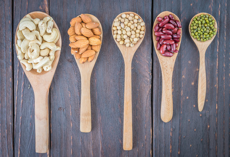 Beans on spoon on wooden background - vintage style picture photo