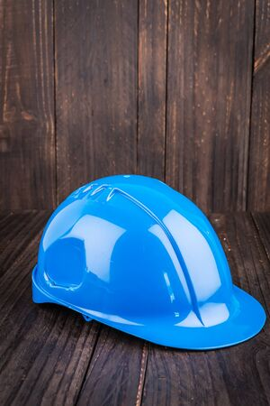 hard wood: Construction hard hat on wooden background