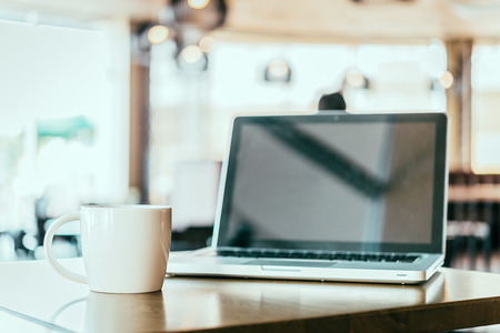 coffee table: Coffee cup and laptop in coffee shop - vintage effect style picture Stock Photo