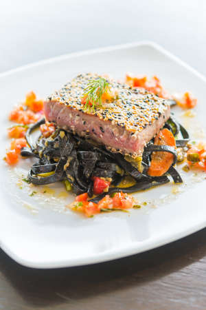 Grilled Tuna fish meat steak with black spaghetti - soft focus point photo