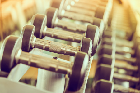 fitness equipment: dumbbells in gym - vintage effect and sun flare filter effect