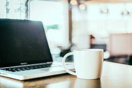 tazas de cafe: Taza de caf�, ordenador port�til en la cafeter�a
