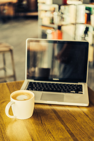 Hot latte coffee cup and laptop in coffee shop - vintage effect style pictures