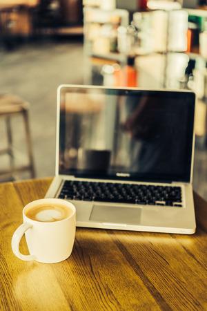 Hot Latte Kaffeetasse und Laptop im Café - Vintage-Effekt-Stil Bilder Lizenzfreie Bilder