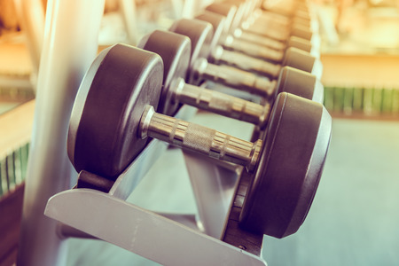dumbbells: dumbbell in gym - vintage effect and sun flare filter effect Stock Photo