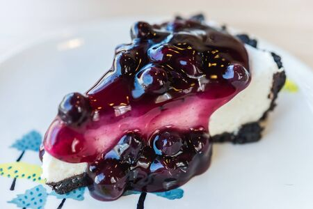 cheese cake: Blueberry cheese cakes in white plate on wooden table - selective focus