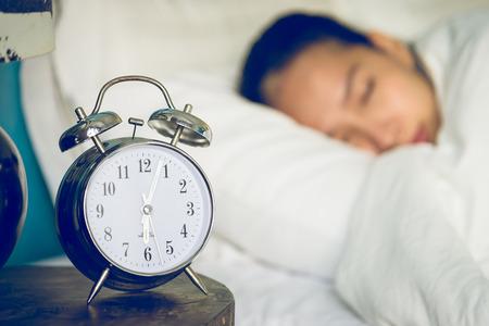 despertador: Reloj en dormitorio con mujer dormida Foto de archivo