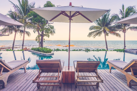 resort: Resort pool with umbrella and chair - vintage filter effect Stock Photo
