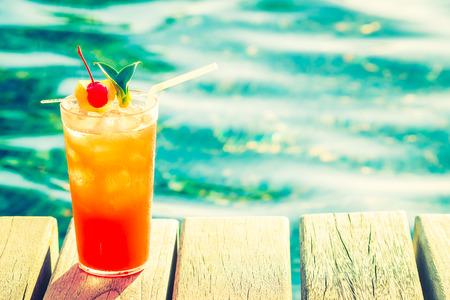 Fruit cocktail glass at pool - vintage filter effect