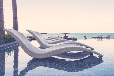 luxury lifestyle: Resort pool with umbrella and chair - vintage filter effect Stock Photo