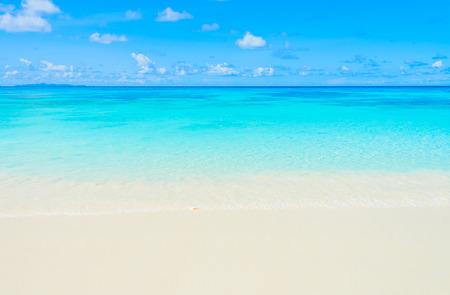 Schönen tropischen Strand und Meer mit blauem Himmel Hintergrund