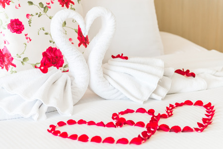 Towel swans and rose flower on bedroom for honeymoon couple - selective focus point photo