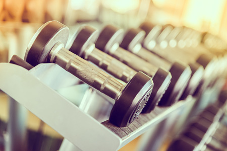 dumbbell: dumbbell in gym - vintage effect and sun flare filter effect Stock Photo