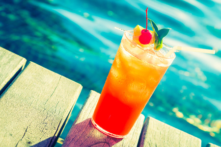 tropical drink: Fruit cocktail glass at pool - vintage filter effect